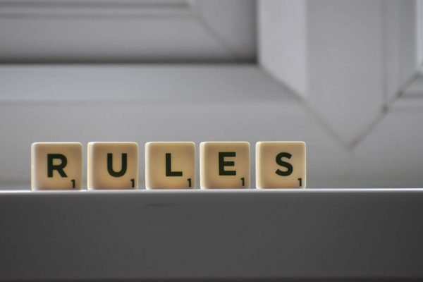Scrabble pieces spell out the word rules